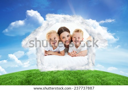 Laughing children playing with their mother lying on a bed against green hill under blue sky - stock photo