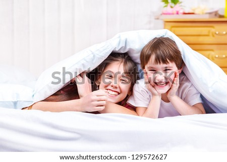 Laughing children under the blanket - stock photo