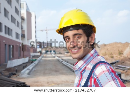 Laughing construction worker with black hair - stock photo