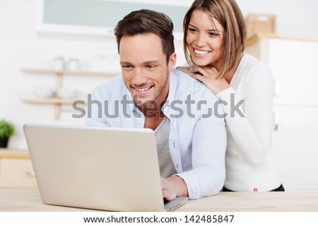 Laughing couple browsing the internet at the laptop - stock photo