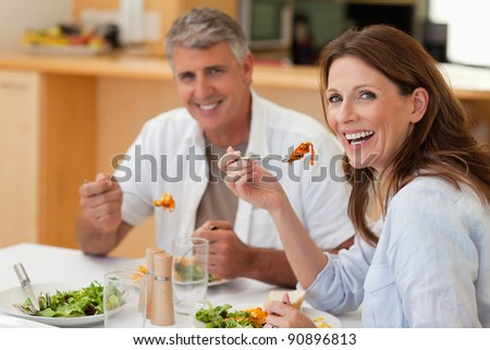 Laughing couple eating dinner together - stock photo