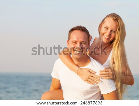 Laughing couple enjoying nature over sea background. Attractive man and woman at the beach. Summer Vacation - stock photo