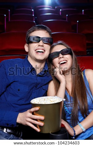 Laughing couple in cinema - stock photo