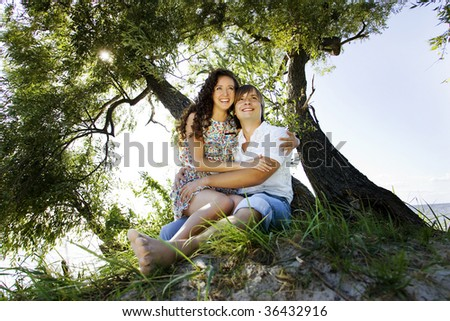 Laughing couple on the island under the tree. - stock photo