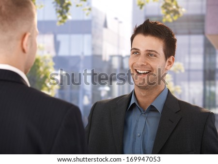 Laughing coworkers standing outside of business office, talking. - stock photo