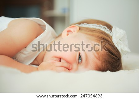 laughing cute girl laying on bed - stock photo
