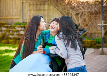 Laughing disabled boy in wheelchair being hugged and kissed by two teenage girls on patio outdoors - stock photo