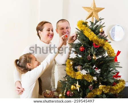 Laughing family of three preparing for Christmas in living room. Focus on woman - stock photo