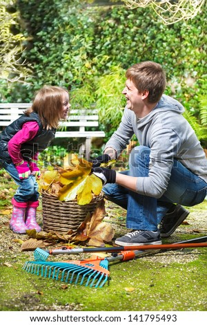 Laughing father and daughter in the autumnal backyard - stock photo