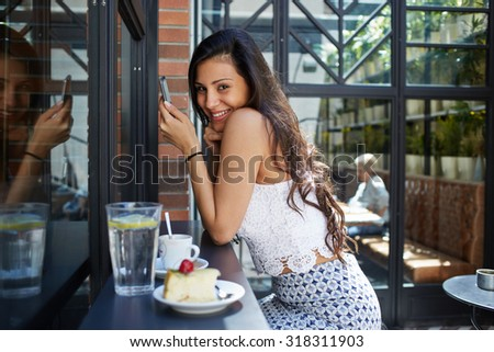 Laughing female brunette with long beautiful hair dressed in a trendy clothes chatting on her smart phone, young woman having breakfast in open air cafe while connecting to wireless via mobile phone - stock photo