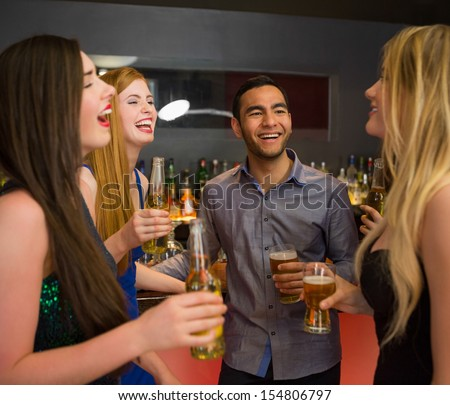 Laughing friends chatting and drinking beer in the nightclub - stock photo