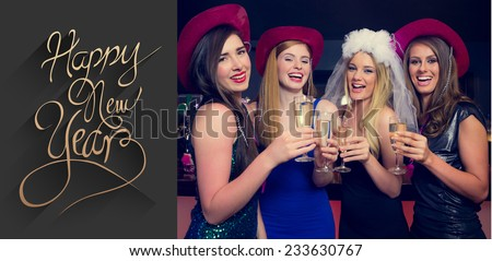 Laughing friends clinking champagne glasses at a hen night against classy new year greeting - stock photo