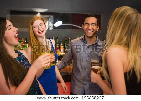 Laughing friends drinking beers and chatting in the nightclub - stock photo