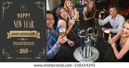 Laughing friends raising their glasses up against art deco new year greeting - stock photo