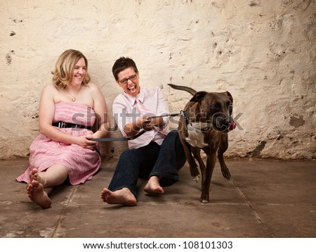 Laughing friends sitting on the floor with funny dog - stock photo