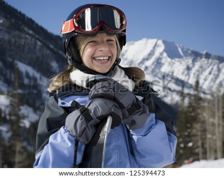 Laughing girl holding snowboard - stock photo