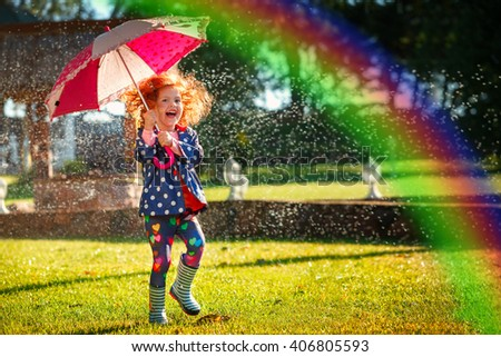 Laughing girl in the rain under umbrella with a rainbow.Happy and healthy childhood concept. - stock photo