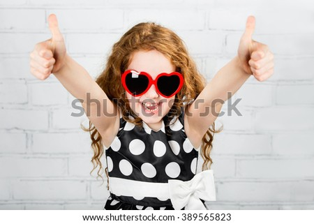 Laughing girl with sunglasses in heart shape, showing thumbs up. - stock photo