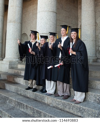 Laughing graduates posing the thumb-up in front of the university - stock photo