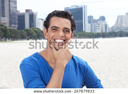 Laughing guy in a blue shirt with cityscape in the background - stock photo