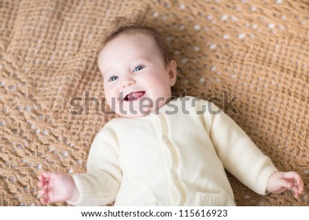 Laughing happy baby in a warm cardigan on a handmade knitted blanket - stock photo