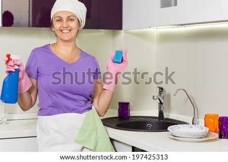 Laughing happy housewife working in the kitchen holding up a pray bottle of detergent and soap as she stands alongside the sink - stock photo