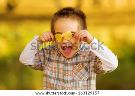 Laughing happy kid playing with autumn leaves outdoors in a park (Shallow DOF) - stock photo