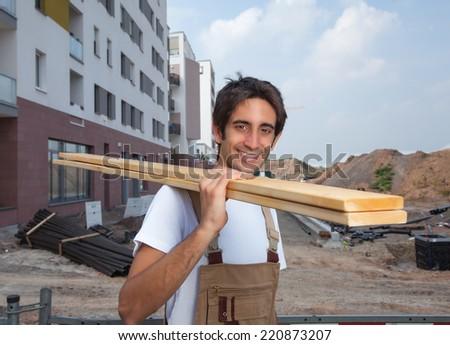 Laughing hispanic carpenter on construction site - stock photo