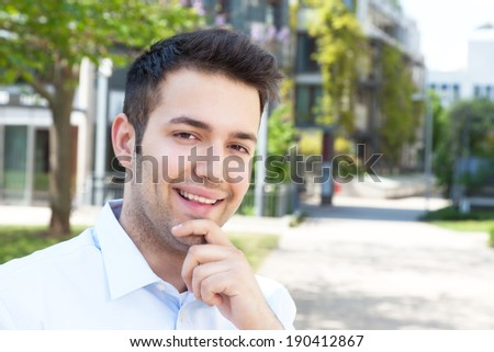 Laughing hispanic male student looking at campus - stock photo