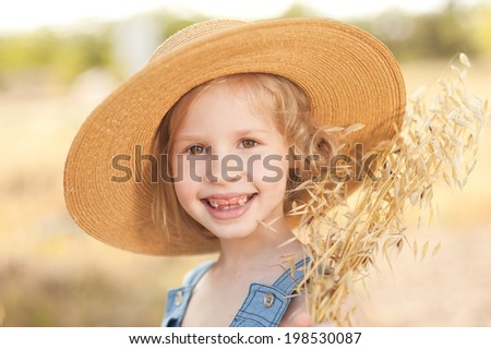 Laughing kid girl wearing hat outdoors - stock photo