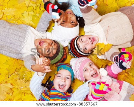 Laughing kids on autumnal leaves - stock photo