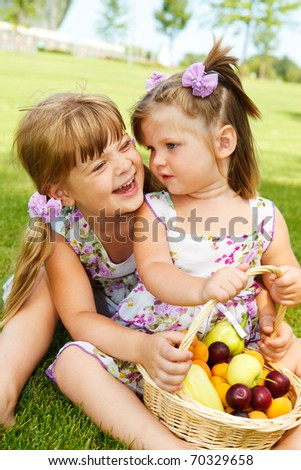 Laughing kids sit with fruit basket in the garden - stock photo