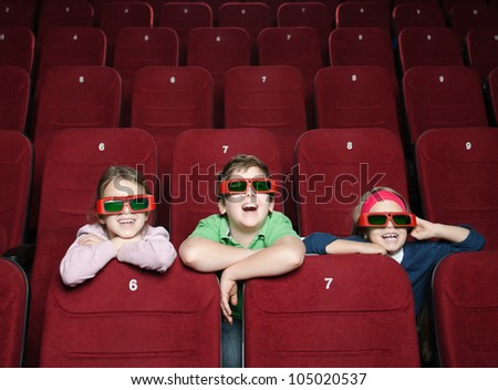 Laughing kids watching a movie - stock photo