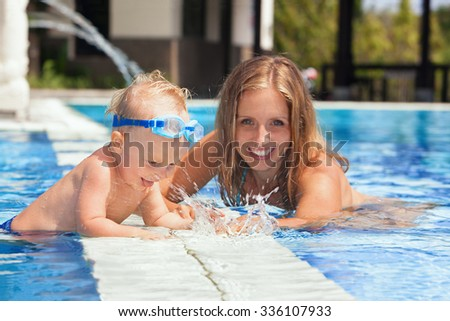 Laughing little baby boy in underwater goggles with happy mother having fun in pool before swimming lesson. Healthy lifestyle, water sport activity with active parents on family vacation with child. - stock photo