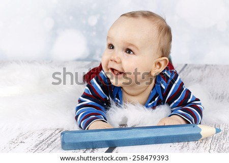 Laughing little baby boy with big crayon - stock photo