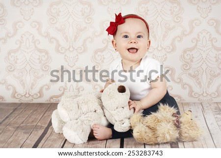 Laughing little baby girl with plush toys - stock photo