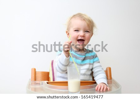 Laughing little blonde toddler girl in blue stripes sweater drinking milk from the glass with straw sitting indoors in high feeding chair against white wall - stock photo