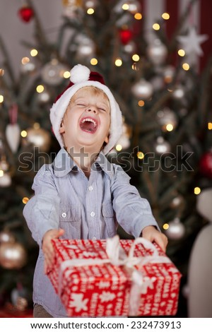 Laughing little boy in a Santa hat holding Christmas gift in his hands in front of the decorated tree - stock photo