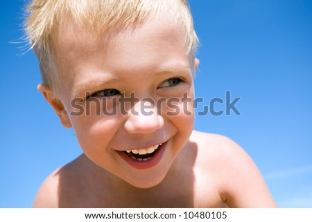 laughing little boy on a background of the sky - stock photo