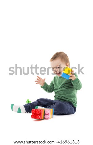 Laughing little boy playing with colorful blocks isolated on white background - stock photo