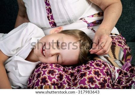 laughing little boy with close eyes and his loving grandmother horizontal - stock photo