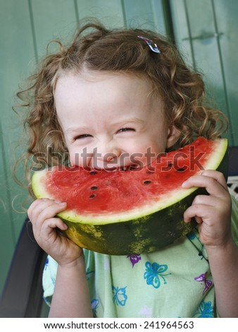 Laughing little girl eating watermelon - stock photo