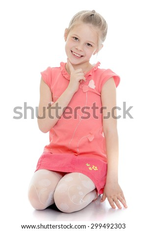 Laughing little girl in a pink t-shirt with short sleeves and a short skirt on her knees cute looking at the camera-Isolated on white background - stock photo