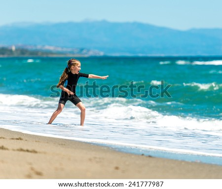 laughing  little girl playing in a wetsuit on the seashore - stock photo