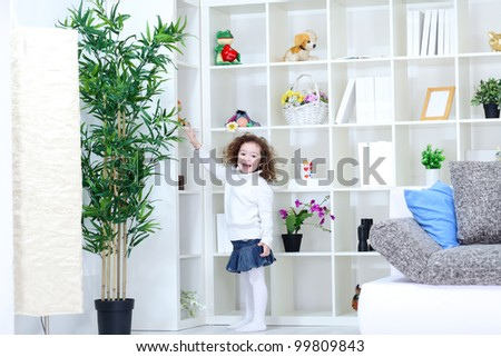 laughing little girl returns to the place of her toys after playing - stock photo
