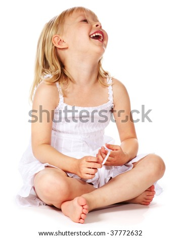 laughing little girl sitting on floor - stock photo