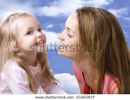 laughing little girl with a mother on a background sky - stock photo