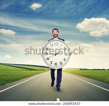 laughing man walking on the road and holding big white clock - stock photo