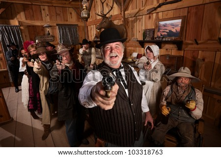 Laughing man with old west gang point guns in a saloon - stock photo