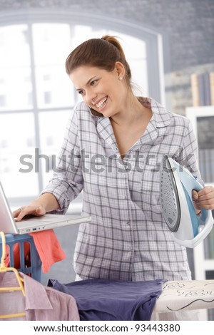 Laughing modern woman multitasking at home, using computer and cellphone, ironing clothes.? - stock photo
